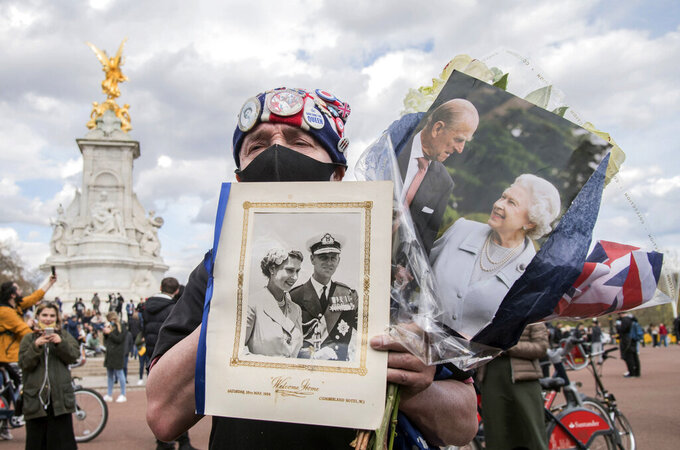 Royal superfan John Loughrey outside Buckingham Palace following the announcement of the death of Britain's Prince Philip, in London, Friday, April 9, 2021. Prince Philip, the irascible and tough-minded husband of Queen Elizabeth II who spent more than seven decades supporting his wife in a role that both defined and constricted his life, has died, Buckingham Palace said Friday. He was 99. (Ian West/PA via AP)