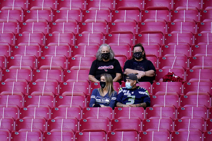 Arizona Cardinals and Seattle Seahawks fans watch their teams prior to an NFL football game, Sunday, Oct. 25, 2020, in Glendale, Ariz. (AP Photo/Ross D. Franklin)
