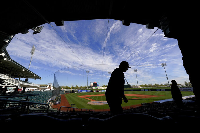 Workers zip tie seats so they can't be used in an effort to encourage social distancing at Surprise Stadium Friday, Feb. 26, 2021, in Surprise, Ariz. The men were working to prepare the venue for Sunday's opening spring training baseball game between the Kansas City Royals and the Texas Rangers. (AP Photo/Charlie Riedel)