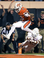 FILE - In this Oct. 27, 2018, file photo, Oklahoma State wide receiver Tylan Wallace (2) jumps across the goal line while evading Texas defensive back Brandon Jones (19) in the first half of an NCAA college football game in Stillwater, Okla. Wallace was selected an AP preseason All-American after being a second-team selection after last season. (AP Photo/Brody Schmidt, File)