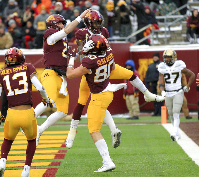 Minnesota tight end Jake Paulson (80) celebrates his touchdown catch with teammates Tanner Morgan (2), Tyler Johnson (6) and Rashod Bateman (13) with Purdue Navon Mosley (27) looks on in the second quarter of an NCAA college football game Saturday, Nov. 10, 2018, in Minneapolis. (AP Photo/Andy Clayton-King)