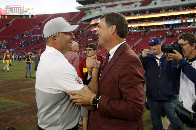 FILE - In this Saturday, Nov. 23, 2019, file photo, Southern California head coach Clay Helton, left, shakes hands with athletic director Mike Bohn at an NCAA college football game against UCLA in Los Angeles. Helton is 40-22 in four full seasons as USC coach. (AP Photo/Marcio Jose Sanchez, File)
