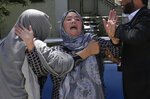 A woman cries at a hospital after she lost her son in a suicide attack on a voter registration center in Kabul, Afghanistan, Sunday, April 22, 2018.  Gen. Daud Amin, the Kabul police chief, said the suicide bomber targeted civilians who had gathered to receive national identification cards. (AP Photo/Massoud Hossaini)