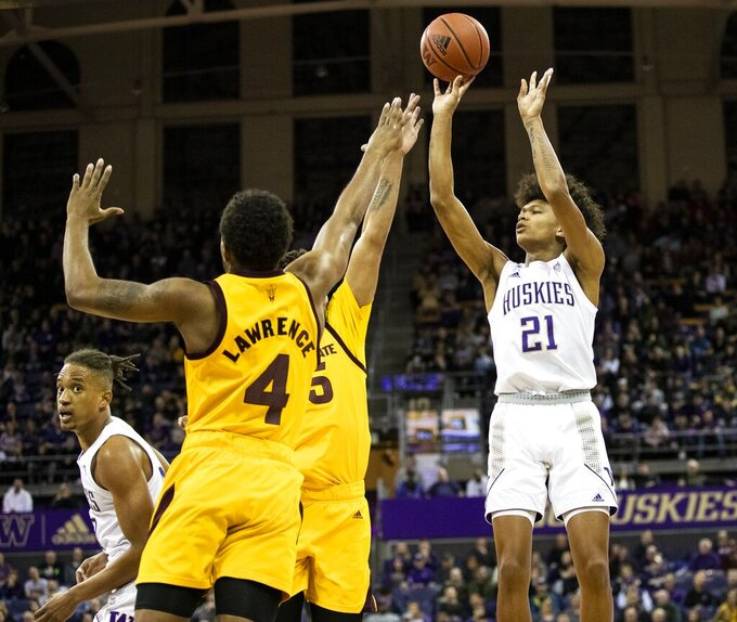 Washington  forward RaeQuan Battle (21) hits a 3-pointer over Arizona State's Kimani Lawrence (4) and another defender during an NCAA college basketball game Saturday, Feb. 1, 2020, in Seattle. (Amanda Snyder/The Seattle Times via AP)