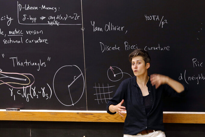 FILE - In this Aug. 7, 2017 photo, mathematics professor Moon Duchin speaks to attendees during a conference at Tufts University in Medford, Mass.  When Virginians voted last year to create a commission to draw the state's political districts, many hoped to head off the partisanship that has marred previous redistricting efforts. Duchin, who specializes in geometry, has been immersed in redistricting problems since 2016, when she taught a class on voting theory. (AP Photo/Bill Sikes)