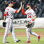 Washington Nationals relief pitcher Ryan Madson (44) and right fielder Bryce Harper (34) celebrate the Nationals 8-6 victory over the New York Mets in a baseball game Monday, April 16, 2018, in New York. (AP Photo/Kathy Willens)