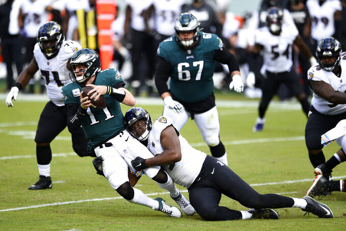 FILE - In this Oct. 18, 2020, file photo, Philadelphia Eagles' Carson Wentz (11) is tackled by Baltimore Ravens' Calais Campbell (93) during the second half of an NFL football game in Philadelphia. In the midst of an NFL season that is course to set records for the most points and touchdowns, the Baltimore Ravens and Pittsburgh Steelers are winning on the strength of their defense.(AP Photo/Derik Hamilton, File)