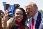 President Donald Trump takes a selfie with a supporter as he arrives at General Mitchell International Airport, Friday, July 12, 2019, in Milwaukee. (AP Photo/Alex Brandon)
