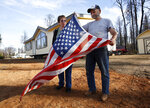 Joyce and Jerry McLean unfurl an American flag outside their new modular home that was recently moved in to replace their home that was destroyed by last year's Camp Fire, in Paradise, Calif., Tuesday, Nov. 5, 2019. The McLean's home is one of nearly 9,000 Paradise homes destroyed in the deadliest and most destructive wildfire in California history. Days after the fire Jerry McLean found the flag still flying in front of the burned out remains of the couple's home. (AP Photo/Rich Pedroncelli)