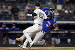 Toronto Blue Jays' Lourdes Gurriel Jr. scores on a wild pitch by New York Yankees' Lucas Luetge (63), who covers the plate during the fourth inning of a baseball game Wednesday, Sept. 8, 2021, in New York. (AP Photo/Adam Hunger)