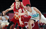 Germany's Niels Giffey (5), left, and Slovenia's Luka Doncic (77) fight for a loose ball during men's basketball quarterfinal game at the 2020 Summer Olympics, Tuesday, Aug. 3, 2021, in Saitama, Japan. (AP Photo/Charlie Neibergall)