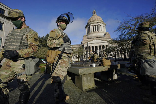 Members of the Washington National Guard stand at a sundial near the Legislative Building, Sunday, Jan. 10, 2021, at the Capitol in Olympia, Wash. Governors in some states have called out the National Guard, declared states of emergency and closed their capitols over concerns about potentially violent protests. (AP Photo/Ted S. Warren)