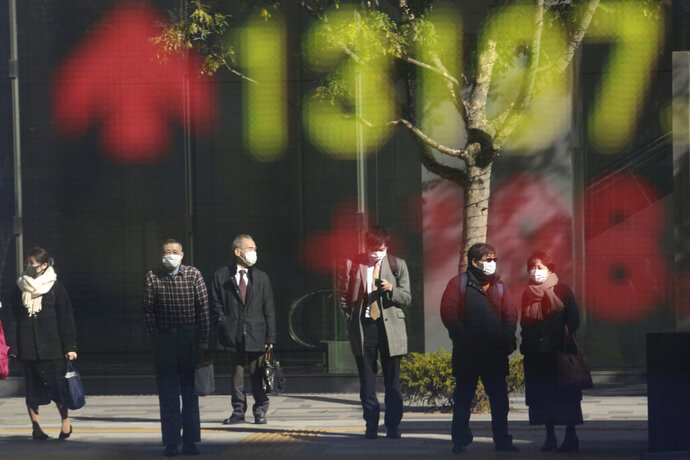 People are reflected on the electronic board of a securities firm in Tokyo, Wednesday, Jan. 20, 2021. Asian shares were mostly higher Wednesday, ahead of Joe Biden's inauguration as president, ending President Donald Trump's four-year term. Japan's benchmark lost early gains as worries grew about the surge in coronavirus cases. (AP Photo/Koji Sasahara)