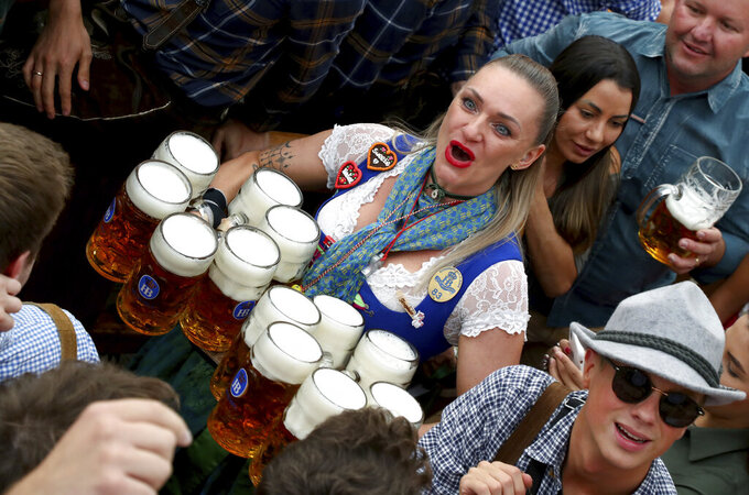 FILE - In this Saturday, Sept. 21, 2019 file photo, a waitress holds twelve glasses of beer during the opening of the 186th 'Oktoberfest' beer festival in Munich, Germany. Official data show that beer sales in Germany were down 5.5 percent last year, dragged lower by lengthy closures of bars and restaurants in the coronavirus pandemic. (AP Photo/Matthias Schrader, file)