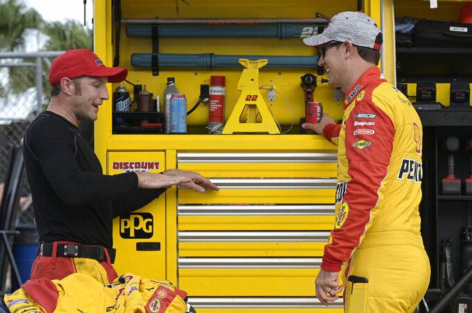 Driver Joey Logano, right, talks with a crew member on pit road before a NASCAR Cup Series auto race at Daytona International Speedway, Saturday, Aug. 28, 2021, in Daytona Beach, Fla. (AP Photo/Phelan M. Ebenhack)