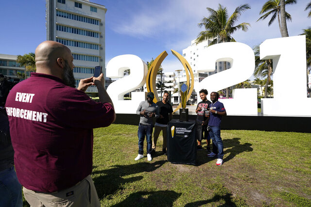 Fans pose with the College Football Playoff championship trophy, Thursday, Jan. 7, 2021, along Ocean Drive in Miami Beach, Fla. Alabama and Ohio State will play in the championship NCAA college football game Jan. 11 at Hard Rock Stadium in Miami Gardens, Fla. (AP Photo/Lynne Sladky)