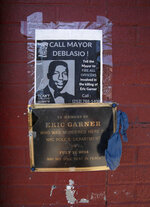 A sign and plaque are mounted on a wall at the sidewalk area where Eric Garner was apprehended by police in the Staten Island borough of New York, Tuesday, July 16, 2019.  Federal prosecutors won't bring charges against New York City police officer Daniel Pantaleo in the 2014 chokehold death of Garner. (AP Photo/Mark Lennihan)