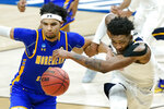 Morehead State's Johni Broome, left, and West Virginia's Derek Culver, right, chase down a loose ball during the second half of a college basketball game in the first round of the NCAA tournament at Lucas Oil Stadium Saturday, March 20, 2021, in Indianapolis. (AP Photo/Mark Humphrey)