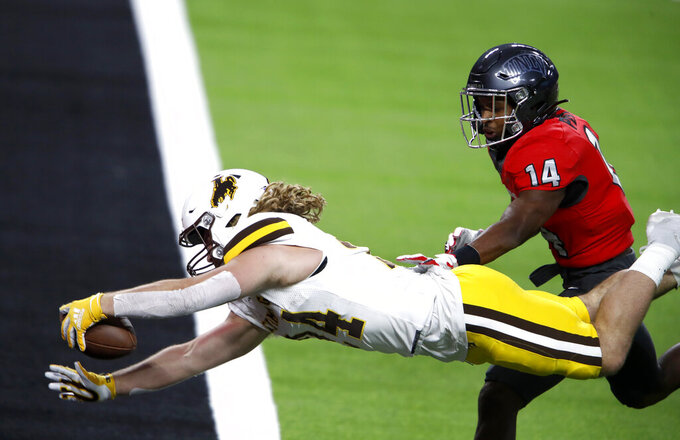 Wyoming running back Brett Brenton (24) dives into the end zone for a touchdown ahead of UNLV defensive back Tyson Player (14) during the second half of an NCAA college football game in Las Vegas on Friday, Nov. 27, 2020. (Steve Marcus/Las Vegas Sun via AP)