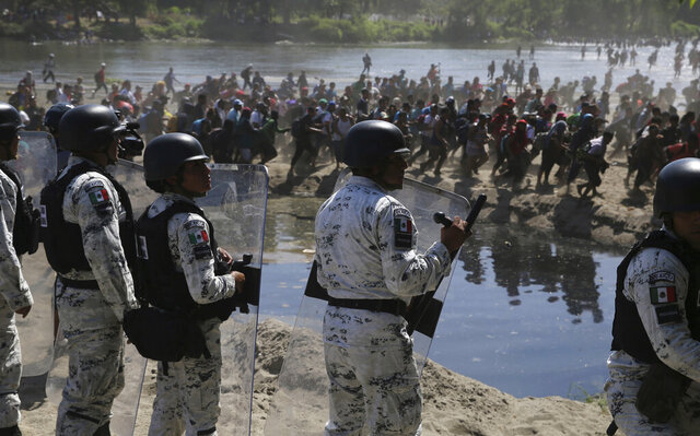 Mexican National Guards stand on the bank of the Suchiate River where Central American migrants are crossing from Guatemala, near Ciudad Hidalgo, Mexico, Monday, Jan. 20, 2020. More than a thousand Central American migrants hoping to reach United States marooned in Guatemala are walking en masse across a river leading to Mexico in an attempt to convince authorities there to allow them passage through the country. (AP Photo/Marco Ugarte)