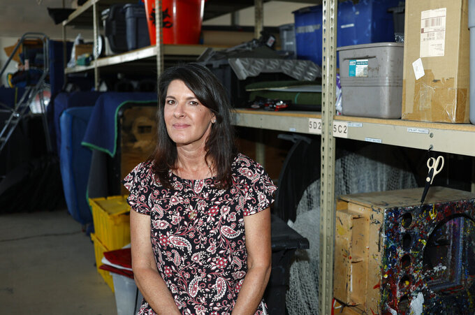 In this Friday, June 5, 2020 photo,, Dawn Abbott, chief executive officer of Fun Productions, a small corporate events company that she started in 1991, is shown amid the myriad unused items stacked in the company's northeast Denver warehouse. The woman's events business was hit hard by concellations with the spread of the new coronavirus and now, three months into the downturn, she does not foresee a quick rebound in the future of her enterprise. (AP Photo/David Zalubowski)