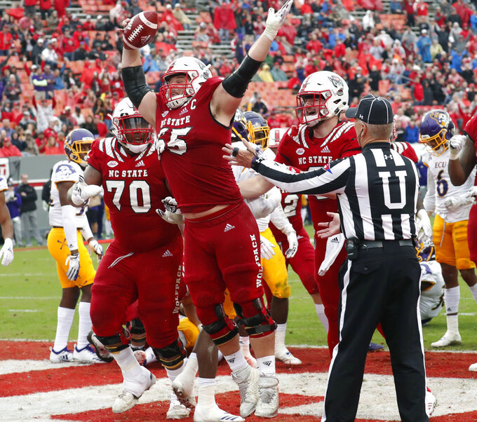 North Carolina State's Garrett Bradbury (65) celebrates after he scored a touchdown during the second half of NCAA college football game in Raleigh, N.C., Saturday, Dec. 1, 2018. (AP Photo/Chris Seward)