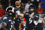 Cincinnati quarterback Desmond Ridder (9) passes to running back Michael Warren II, left, during the first half of the team's NCAA college football game against UCF, Friday, Oct. 4, 2019, in Cincinnati. (AP Photo/John Minchillo)