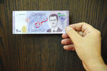 FILE - In this July 2, 2017 file photo released by the Syrian official news agency SANA, a man displays a new bank note of 2,000 Syrian Lira, during a press conference for the Syria's Central Bank Governor, in Damascus, Syria. In Syria nowadays, there is an impending fear that all doors are closing. After nearly a decade of war, the country is crumbling under the weight of years-long western sanctions, government corruption and infighting, a pandemic and an economic downslide made worse by the financial crisis in Lebanon, Syria's main link with the outside world. (SANA via AP, File)