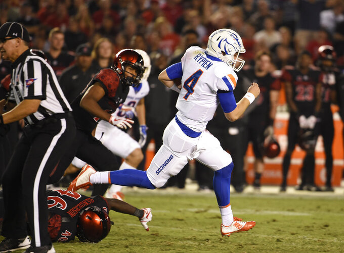 FILE - In this Oct. 14, 2017, file photo, Boise State quarterback Brett Rypien (4) breaks away from San Diego State defenders on a long run during the first half of an NCAA college football game, in San Diego.  Rypien is about to become a rarity in college football, a quarterback with the skill from the outset of his arrival on campus to be the starter for the vast majority of his four years at Boise State. (AP Photo/Denis Poroy, File)