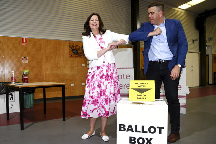 Queensland Premier Annastacia Palaszczuk and the member for Oxley Milton Dick bump elbows after casting their votes in the state election, at the Inala State School polling booth in Brisbane, Australia Saturday, Oct. 31, 2020. Australia's tourist-popular Queensland state is voting for a new government Saturday in an expected close race between incumbent Premier Palaszczuk's Labor Party and Liberal National Party leader Deb Frecklington. (Dan Peled/Pool Photo via AAP Image)
