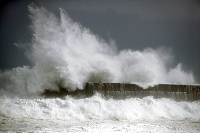 In this Wednesday, Aug. 14, 2019, photo, high waves hit a fishing port in Kochi, southwestern Japan as a powerful typhoon Krosa approaches southern and western Japan. (Suo Takekuma/Kyodo News via AP)