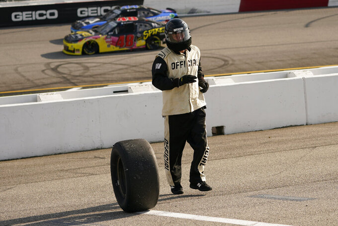 A NASCAR official retrieves a loose tire from pit row during the NASCAR Xfinity auto race in Richmond, Va., Saturday, Sept. 11, 2021. (AP Photo/Steve Helber)