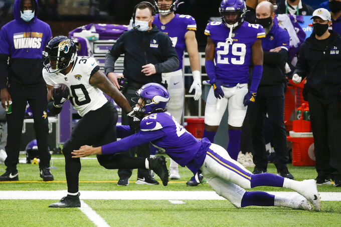 Jacksonville Jaguars running back James Robinson tries to break a tackle by Minnesota Vikings linebacker Troy Dye, right, during the first half of an NFL football game, Sunday, Dec. 6, 2020, in Minneapolis. (AP Photo/Bruce Kluckhohn)