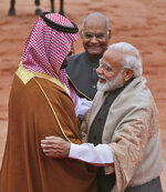 Indian Prime Minister Narendra Modi welcomes Saudi Arabia's Crown Prince Mohammed bin Salman with a hug, as Indian President Ram Nath Kovind stands beside them during a ceremonial welcome in New Delhi, India, Wednesday, Feb. 20, 2019. Prince Mohammed arrived in India after visiting Pakistan, which New Delhi blames for a suicide bombing attack last week that killed at least 40 Indian soldiers in disputed Kashmir. (AP Photo/Manish Swarup)