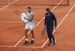 Spain's Rafael Nadal, left, and his coach Francisco Roig wearing a face mask to prevent the spread of coronavirus walk on the clay during practicing at the Roland Garros stadium in Paris, Friday, Sept. 25, 2020. Already repeatedly trimmed, crowd sizes for the French Open have been reduced again to just 1,000 spectators per day because of the worsening coronavirus epidemic in Paris. (AP Photo/Michel Euler)