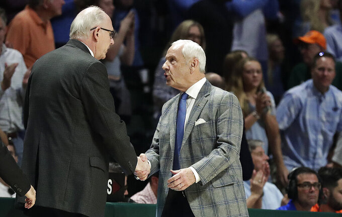 Miami Hurricanes head coach Jim Larranaga, left, and North Carolina Tar Heels head coach Roy Williams, right, greet after an NCAA college basketball game against on Saturday, Jan. 19, 2019, in Coral Gables, Fla. (AP Photo/Brynn Anderson)