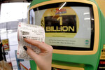 A patron, who did not want to give her name, shows the ticket she had just bought for the Mega Millions lottery drawing at the lottery ticket vending kiosk in a Smoker Friendly store, Friday, Jan. 22, 2021, in Cranberry Township, Pa. The jackpot for the Mega Millions lottery game has grown to $1 billion ahead of Friday night's drawing after more than four months without a winner. (AP Photo/Keith Srakocic)