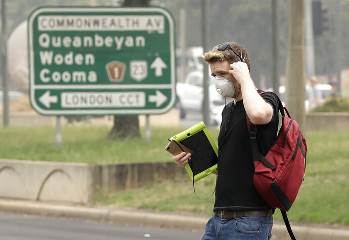 A pedestrian wears a mask as smoke shrouds the Australian capital of Canberra, Australia, Thursday, Jan. 2, 2020. Australia deployed military ships and aircraft to help communities ravaged by apocalyptic wildfires that destroyed homes and sent thousands of residents and holidaymakers fleeing to the shoreline. (AP Photo/Mark Baker)