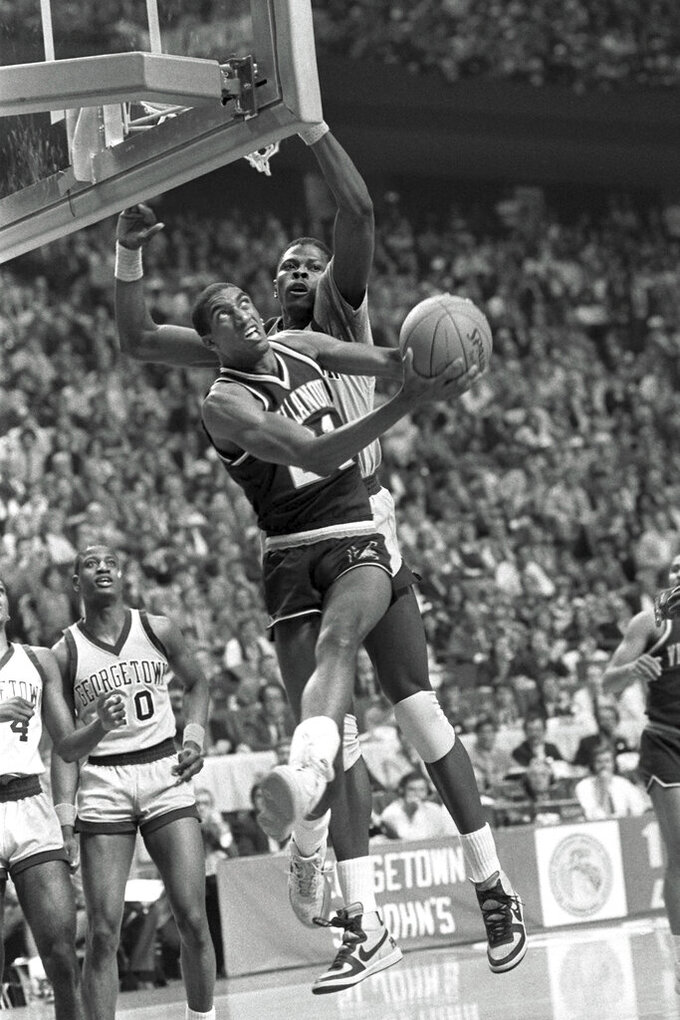 FILE - In this April 1, 1985, file photo, Villanova's Harold Pressley (21) goes up for a basket against Georgetown's Patrick Ewing in the NCAA college basketball Final Four championship game, in Lexington, Ky. Underdog Villanova, shooting 79 percent from the field, denied Patrick Ewing and top-ranked Georgetown a second straight NCAA basketball title Monday night with a 66-64 victory. (AP Photo/John Swart, File)