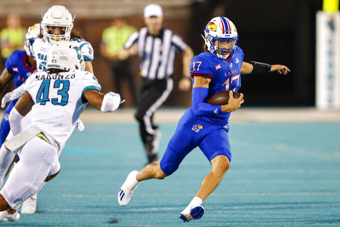 Kansas quarterback Jason Bean (17) carries the football as Coastal Carolina safety Enock Makonzo (43) chases during the first half of an NCAA college football game in Conway, S.C., Friday, Sept. 10, 2021. (AP Photo/Nell Redmond)