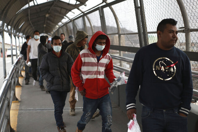 FILE - In this Saturday, March 21, 2020 file photo, Central American migrants seeking asylum, some wearing protective face masks, return to Mexico via the international bridge at the U.S-Mexico border that joins Ciudad Juarez and El Paso. Mexico and the U.S. are restricting travel over their busy shared border as they try to control the spread of the coronavirus pandemic. (AP Photo/Christian Chavez)