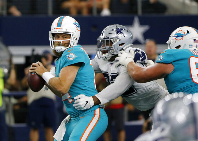 Miami Dolphins quarterback Ryan Fitzpatrick, left, attempts to throw a pass under pressure from Dallas Cowboys' Dorance Armstrong (92) in the first half of an NFL football game in Arlington, Texas, Sunday, Sept. 22, 2019. (AP Photo/Michael Ainsworth)