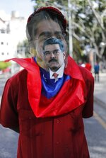 A man wears a make-shift mask with an image of President Nicolas Maduro taped to it, during a pro-government demonstration against TIAR or the Inter-American Treaty of Reciprocal Assistance, in Caracas, Venezuela, Tuesday, Dec. 3, 2019. Representatives from over a dozen nations that are signatories of the Cold War-era defense treaty for the Americas moved Tuesday to further isolate close allies of Maduro with economic sanctions. (AP Photo/Ariana Cubillos)