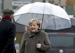 German Chancellor Angela Merkel holds an umbrella as she arrives at the Berlin Wall Memorial in Berlin, Germany, Saturday, Nov. 9, 2019. (AP Photo/Michael Sohn, pool)