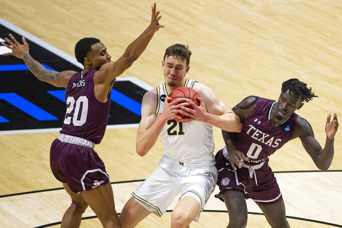 Michigan's Franz Wagner (21) drives between Texas Southern's Michael Weathers (20) and Yahuza Rasas (0) during the first half of a First Round game in the NCAA men's college basketball tournament, Saturday, March 20, 2021, at Mackey Arena in West Lafayette, Ind. (AP Photo/Robert Franklin)