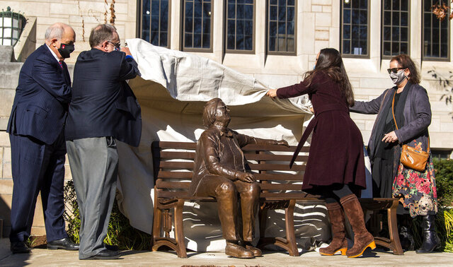President of Indiana University Michael McRobbie, from left, Michael D. McGinnis, Professor Emeritus of Political Science, Jaime Carini, Ostrom Fellow, and Lauren Robel, Provost of Indiana University Bloomington, lift the sheet off of the Elinor Ostrom statue in the Ostrom Commons outside Woodburn Hall at Indiana University Thursday, Nov. 12, 2020, in Bloomington, Ind. The statue of Ostrom was unveiled on the campus where she taught for many years as an IU professor. Ostrom, the first woman to win the Nobel Prize in economics, died in 2012 at age 78. (Rich Janzaruk/The Herald-Times via AP)