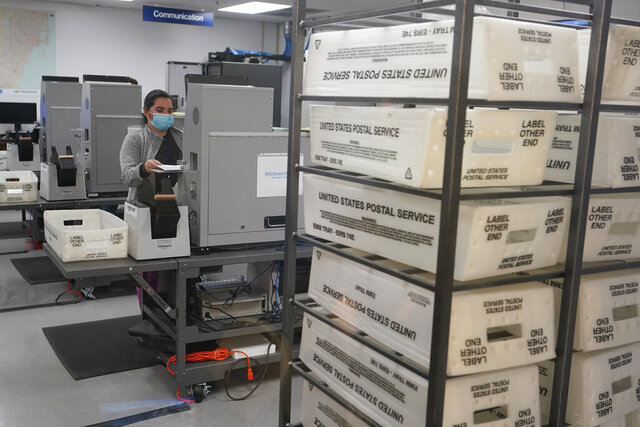 A workers scans and tabulate ballots, Tuesday, Nov. 3, 2020, at the Miami-Dade County Elections Department in Doral, Fla. (AP Photo/Wilfredo Lee)