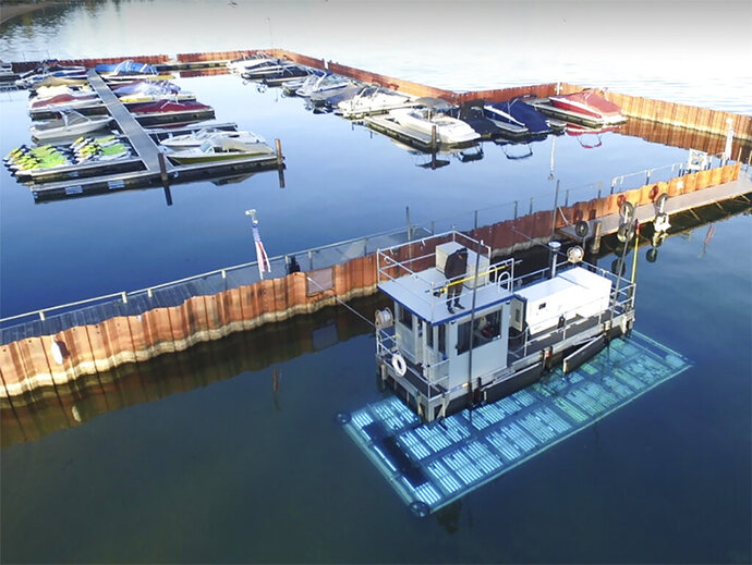 This photo provided by Inventive Resources Inc., shows a boat at the Lakeside Marina in South Lake Tahoe, Calif., equipped with ultraviolet lights that is proving effective at killing algae and other marine plants that eat away at Lake Tahoe's clarity. The UV vessel designed by Inventive Resources Inc. and operated by researchers at the University of Nevada, Reno, is designed to operate in the tight spaces of a marina or the open lake. (Inventive Resources Inc. via AP)
