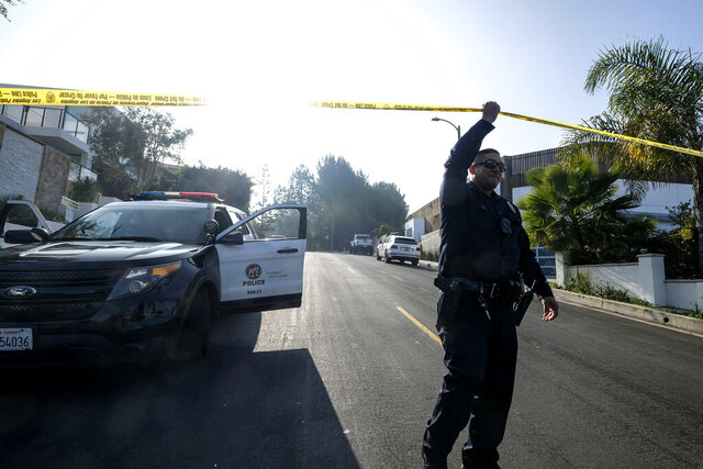 A police officer guards outside a Hollywood Hills home where a fatal shooting occurred on Wednesday, Feb. 19, 2020, in Los Angeles. (AP Photo/Ringo H.W. Chiu)