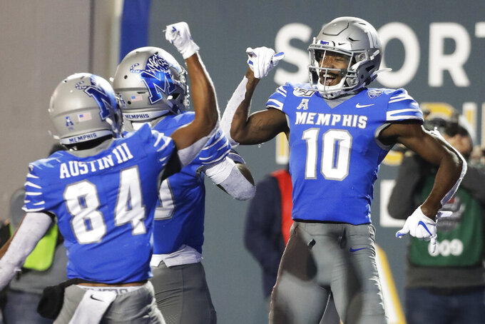 Memphis wide receiver Damonte Coxie (10) celebrates with running back Kenneth Gainwell, center, and wide receiver Calvin Austin III (84) after Coxie caught a 49-yard touchdown pass against SMU during the second half of an NCAA college football game Saturday, Nov. 2, 2019, in Memphis, Tenn. Memphis won 54-48. (AP Photo/Mark Humphrey)